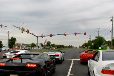 fem superbiler ved et vejkryds med bla aventador